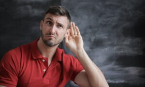 Man Listenening with His Hand to His Ear